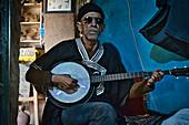 Alter blinder Mann, Berber, spielt im Museum im Dorf Oumesnat ein Instrument, Tal der Ammeln im Antiatlas, Marokko