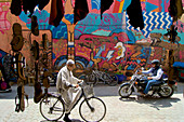 Senior man on bicycle meets tourist on motorbike in front of a brightly painted wall in the old town of Marrakech, Morocco