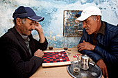 Two old men, Moroccans, fell a board game, lady, and drink tea, Essaouira, Morocco