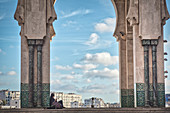 View through arches of the Hassan II mosque on modern buildings, woman in traditional clothing, Casablanca, Morocco