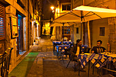 Tables of a small restaurant with two men in the late evening in the alleys of the Cais da Ribeira, Porto, Portugal