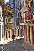 Alley from Torre de Clerigo to Cais da Ribeira with a person and a woman on a balcony. Porto, Portugal