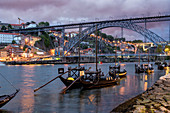 Rabelo boats with port wine barrels, Douro Riverside at dusk, Porto, Portugal