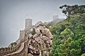 Wall and fortified tower in the fog in Castelo dos Mouros Sintra, Lisbon, Portugal