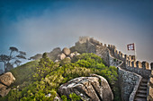 Wall and fortified tower in the raging fog in Castelo dos Mouros Sintra, Lisbon, Portugal