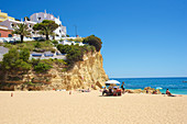 Few people on the beach in bright blue sky in Carvoeiro, Lagoa, Algarve, Portugal
