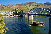 Bridge over the Douro with excursion boat in Pinhão with vineyards, northern Portugal, Portugal