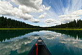 View from a canoe to the mirror-smooth Yukon River, canoe trip from Lake Laberge to Carmacks, Yukon, Canada