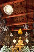 Interior with seated Buddha statue in Wat Arun, Bangkok, Thailand