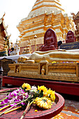 Offerings and Buddha statues in the golden Buddhist temple. Wat Prah That Doi Suthep, Chiang Mai, Thailand