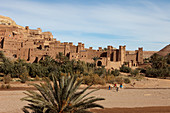 Tourists on camels in front of the walls of the Kasbah Ait Ben Haddou and the desert, Ait Ben Haddou, Morocco