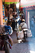 Motorcycles and souvenir shops in the souks of the medina, Marrakech, Morocco