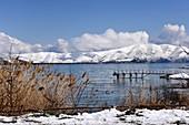 Steg am Ufer des Sees, Blick von der Halbinsel Sewan mit schneebedeckten Bergen, Sewansee, Armenien, Asien