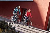 Junges Paar auf eBikes in urbaner Umgebung, München, Bayern, Deutschland