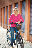 Young woman with eBike in urban environment, Munich, Bavaria, Germany