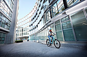 Young woman on bicycle in urban environment, Munich, Bavaria, Germany
