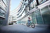 Junge Frau auf Fahrrad in urbaner Umgebung, München, Bayern, Deutschland