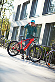 Junge Frau mit eBike an einem Fahrradparkplatz; München, Bayern, Deutschland