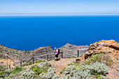 A hiker in Garajonay National Park overlooking the Atlantic Ocean, Agulo, La Gomera, Canary Islands, Spain