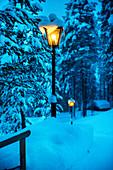 Mit Laternen beleuchteter verschneiter Weg zu einer Holzhütte bei Heggenes, Norwegen