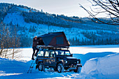 Mann mit Rooftoptent an seinem Geländewagen in Winterlandschaft bei Heggenes, Norwegen