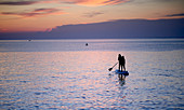 Two girls on a SUP, dusk in front of Susak island, Kvarner bay, Adriatic sea, Croatia
