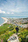 Joggers take the path down to Chesil Beach from Portland heights on the Isle of Portland, Dorset, England, United Kingdom, Europe