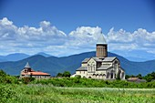 Alaverdi Monastery towering in green landscape with Caucasus mountains in the background, Kakheti, East Georgia