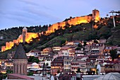 Evening view of the old town and fortress with its houses, churches and part of the city wall, right the cable car station, Tbilisi, Georgia