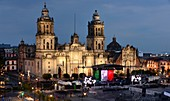 Evening view of the lit Cathedral at the Zocalo with stage and Mexican Flag, Mexico City, Mexico