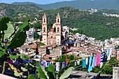 Blick über bunte Wäsche von oben auf die Altstadt und die Igleisia de Santa Prisca von Taxco, Mexiko