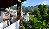 Touistin on a corridor of the Posada de la Mision with palm trees and green hills and white houses in the background, Colonial Taxco, Mexico