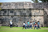Tourists in front of a stepped temple with stone sculptures on the pre-Columbian archaeological site of Xochicalco at Cuernavaca, Mexico