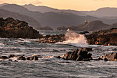 The wild sea whips against the rock on the south coast in Penne, Norway. In the background a lighthouse, mountains and rocks.