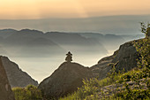 Cairn stands on a rock in the sunrise. In the background mountains in the morning fog and the Lysefjord. Norway