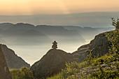 Steinmännchen auf einem Fels bei Sonnenaufgang, dahinter der Lysefjord im Morgennebel, Norwegen