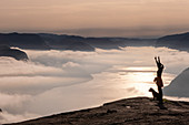 Woman with dog stands on the Preikestolen and shows the peace sign. Behind her the Lysefjord in the Mogennebel and the sunrise. Norway