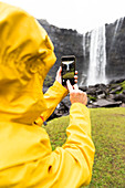 Tourist snaps photos with smartphone, Fossa waterfall, Streymoy island, Faroe Islands, Denmark, Europe