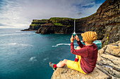 Man with smartphone snaps photos at Gasadalur waterfall, Vagar island, Faroe Islands, Denmark, Europe
