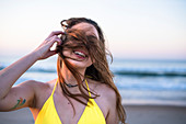 Head and shoulders shot of smiling woman in yellow bikini on beach with windswept hair