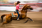 Cowgirl riding horse during barrel race rodeo, Pagosa Springs, Colorado, USA
