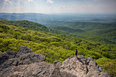 Male hiker standing at edge of Humpback Rock with sunlight illuminating green forest in background, Virginia, USA