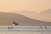 Group of four people paddleboarding in sea at sunset, Vancouver, British Columbia, Canada