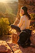 Portrait of female hiker smiling while enjoying sunset at Cathedral Rock, Arizona, USA