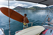 Three quarter length shot of young man carrying surfboard on yacht