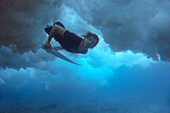 Underwater view of male surfer looking at camera while diving in ocean, Male, Maldives