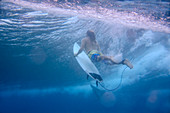 Underwater view of male surfer diving in ocean, Male, Maldives