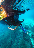 Underwater view of diver standing upside down on sunken shipwreck, Nusa Penida, Bali, Indonesia
