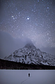 Stars in sky at night above Waterfowl Lake in winter, Banff National Park, Alberta, Canada