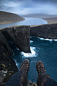 Personal perspective shot with feet of person sitting on edge of coastal cliff, Sorvagsvatn, Faroe Islands